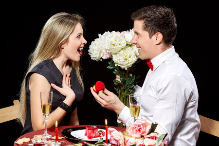 proposing: Man proposing marriage to a surprised woman on black background Stock Photo