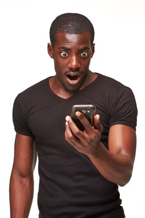 phone conversations: Portrait of surprised african man talking on the phone isolated on a white background