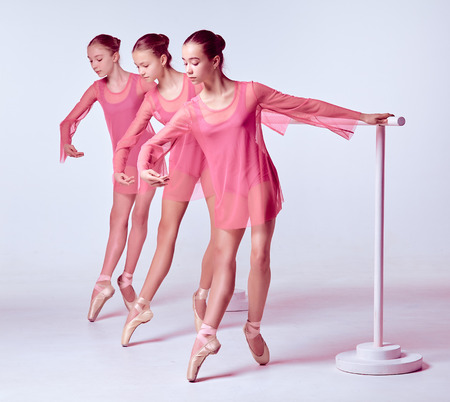 flexable: Three young ballerinas stretching on the bar on beige background