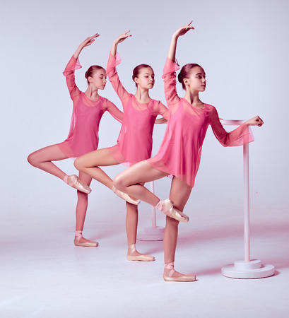 ballet bar: Three young ballerinas stretching on the bar on beige background
