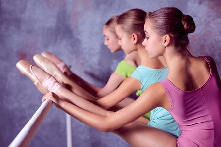 ballet niñas: Tres bailarinas jóvenes se extiende en el bar en el fondo de la lila