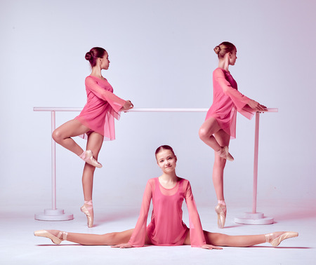 flexable: Three young ballerinas  in a pink dresses stretching on the bar on beige background