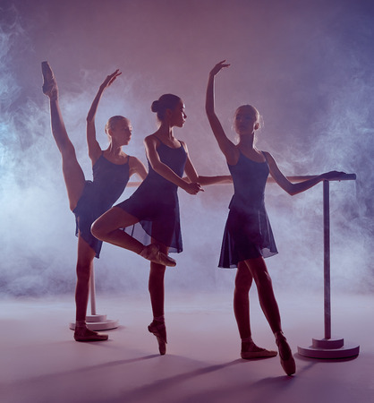 flexable: Three young ballerinas  in blue dresses stretching on the bar on lilac background Stock Photo