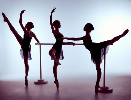 Three young ballerinas stretching on the bar on lilac background