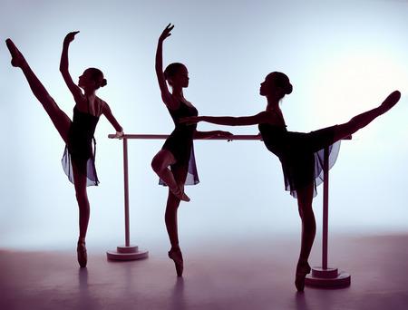 gymnastique: Trois jeunes ballerines étirement sur la barre sur fond lilas Banque d'images