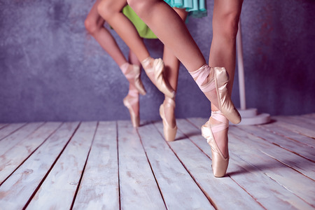 child education: The close-up feet of a three young ballerinas in pointe shoes against the background of the wooden floor