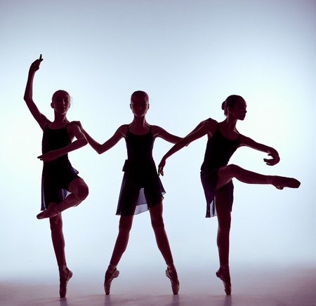 ballet bar: silhouettes of three young dancers in ballet poses on a gray background