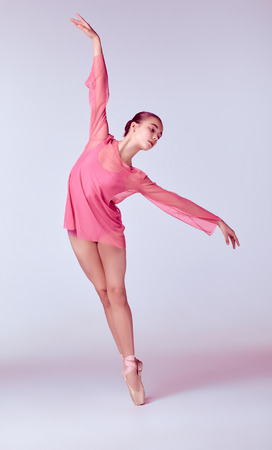 techniques: Young ballerina dancer in pink dress showing her techniques on gray background