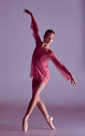 라일락 배경에 그녀의 기술을 보여주는 핑크 드레스 젊은 발레리나 댄서
