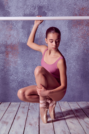 flexable: The young ballerina stretching on the bar on lilac background of wooden floor