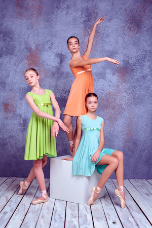flexable: Three young ballerinas in colorful dresses posing on lilac wooden floor background