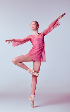 Young ballerina dancer in pink dress showing her techniques on lilac background