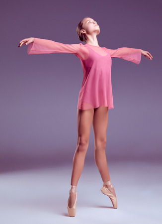 techniques: Young ballerina dancer in pink dress showing her techniques on lilac background