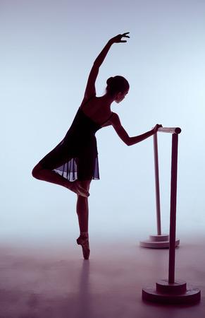 silueta humana: bailarina joven que estira en la barra sobre fondo azul
