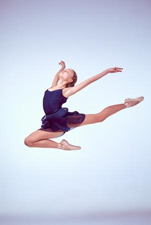 회색 배경에 점프하는 젊은 발레 댄서