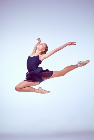 'ballet girl': young ballet dancer jumping on a grey background