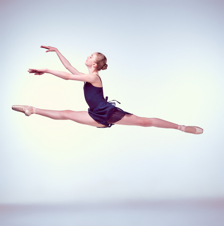 leap: young ballet dancer jumping on a grey background