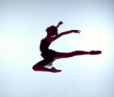 bailarinas: bailarina de ballet joven saltando sobre un fondo gris Foto de archivo