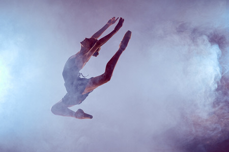 young ballet dancer jumping on a lilac background with smoke effect