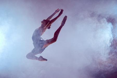 saltando: bailarina de ballet joven saltando sobre un fondo lila con efecto de humo