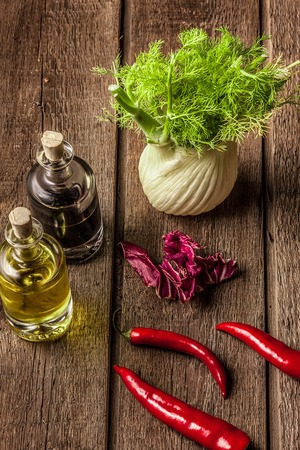 recently: fresh olive oil, balsamic vinegar, red pepper pods and bay leaves on wooden table.  Stock Photo