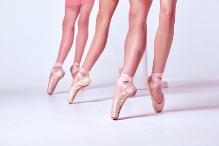 classic art: The close-up feet of a three young ballerinas in pointe shoes on beige background