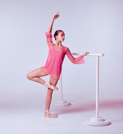 flexable: The young ballerina stretching on the bar on gray background Stock Photo