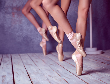 ballerina girl: The close-up feet of a three young ballerinas in pointe shoes against the background of the wooden floor