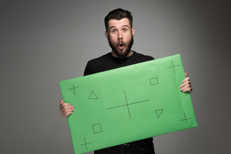 The surprised man as businessman with green panel on gray background photo