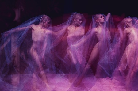 a sensual and emotional dance of beautiful ballerina through the veil on a dark background Stock Photo