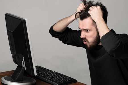 Funny and crazy man using a computer on gray background photo