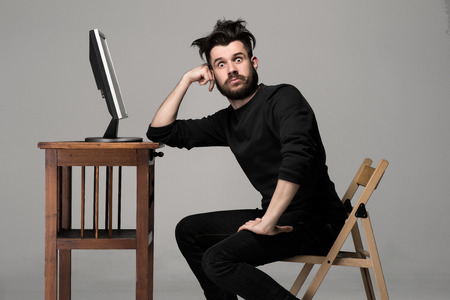 Funny and crazy man using a computer on gray background 版權商用圖片 - 40507085
