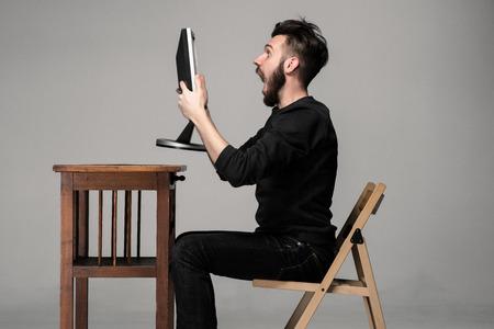 caras graciosas: Hombre divertido y loco uso de una computadora en el fondo gris, celebración de un monitor