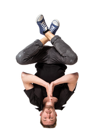breakdancing: Young handsome fresh man breakdancing standing on his head, isolated on white background