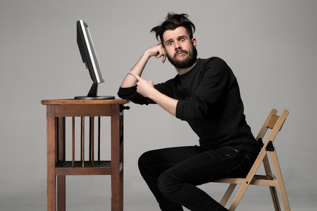 sorpresa: Hombre divertido y loco uso de una computadora en el fondo gris