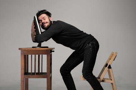caras graciosas: Hombre divertido y loco uso de una computadora en el fondo gris