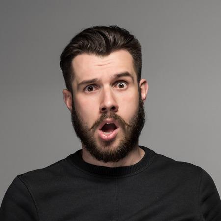asustado: Retrato de un joven empresario desconcertado con la boca abierta sobre fondo gris
