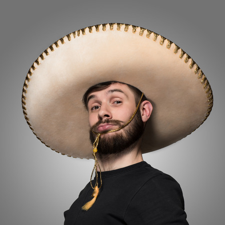 portrait of funny man in Mexican sombrero on gray background