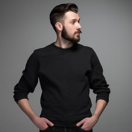 Retrato de la manera ofprofile de hombre joven en poses negras sobre fondo gris. mirar hacia