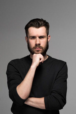 conceited: Fashion portrait of young thoughtful man in black  poses over gray background