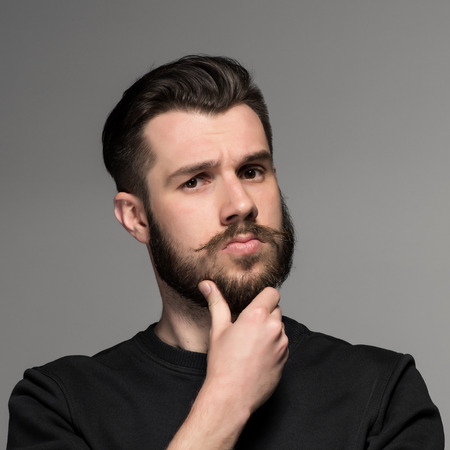 enticement: Fashion portrait of young thoughtful man in black  poses over gray background