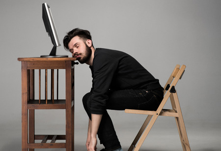 Businessman sleeping near monitor of computer on gray background