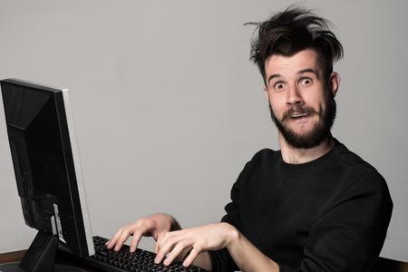 gente loca: Hombre divertido y loco uso de una computadora en el fondo gris