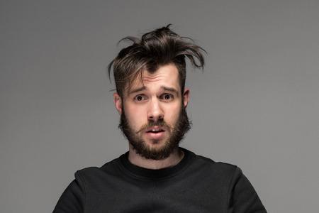 zerzaust: Portr�t der jungen Mann mit einem zerzausten Bart und Schnurrbart auf grauem Hintergrund