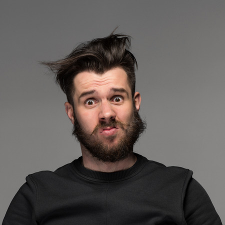 tousled: Portrait of young tousled man with a beard and mustache on gray background