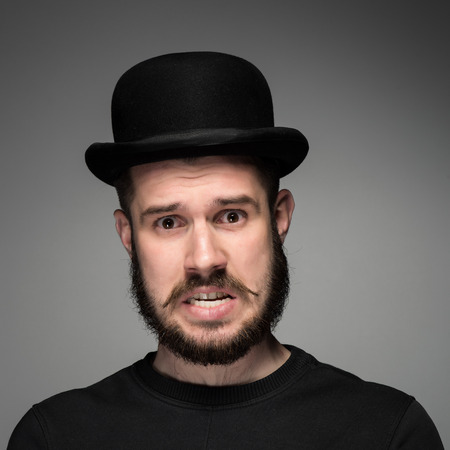 indignant: Portrait of young indignant, huddled teeth man with a beard and mustache in black hat on gray background. concept of discontent Stock Photo