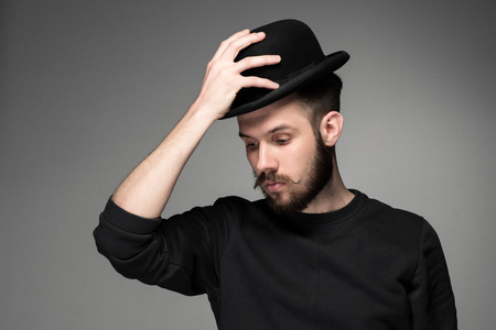 admiration: Young man with a mustache and beard raising his hat  in respect and admiration for someone. portrait on gray background. male gaze directed downward Stock Photo