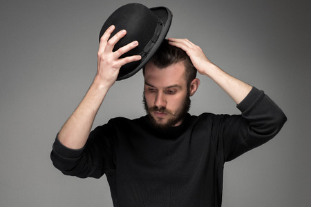 man hat: Young man with a mustache and beard raising his hat  in respect and admiration for someone. portrait on gray background. male gaze directed downward Stock Photo