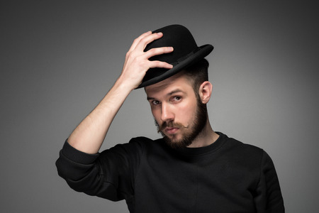 admiration: Young man with a mustache and beard raising his hat  in respect and admiration for someone. portrait on gray background. Stock Photo
