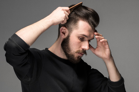 young man comb his hair on gray background